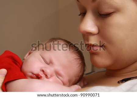 Sleeping baby boy wearing a red shirt on his mother's chest. - stock photo