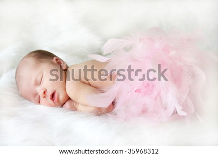 Sleeping baby covered in pink feathers with a soft focus for elegance.