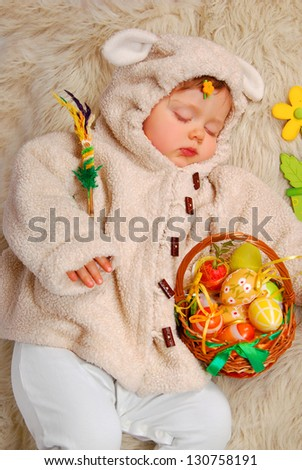 sleeping baby girl as easter sheep holding wicker basket with colorful eggs - stock photo