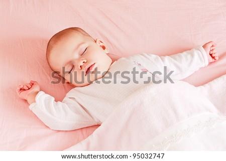 Sleeping baby girl in bed under blanket - stock photo