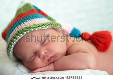 Sleeping baby girl wearing a striped hat - stock photo