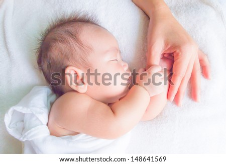 sleeping baby holding mom hand - stock photo