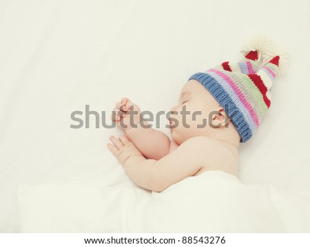 sleeping baby in a funny striped hat