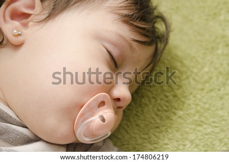 sleeping baby in close up image with pacifier. - stock photo