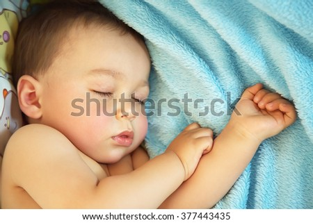 sleeping baby. little boy lying in a crib on a blue blanket - stock photo