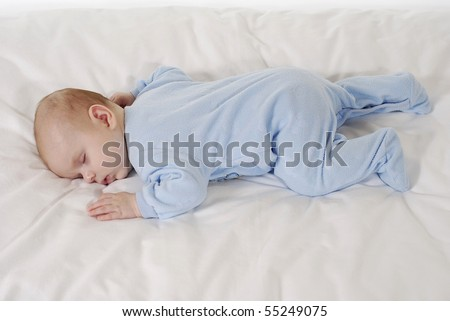sleeping baby lying on her stomach in blue clothes on the white background - stock photo