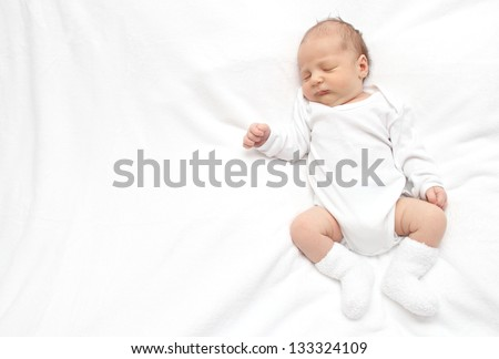 Sleeping baby on back on white bed - stock photo