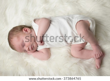 Sleeping baby on white blanket
