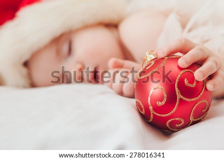 Sleeping baby Santa Claus red hat and focus on hand whith Christmas tree decoration - stock photo