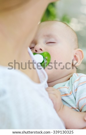 sleeping baby with a pacifier in mother's arms - stock photo