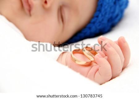 Sleeping baby with wedding rings - stock photo