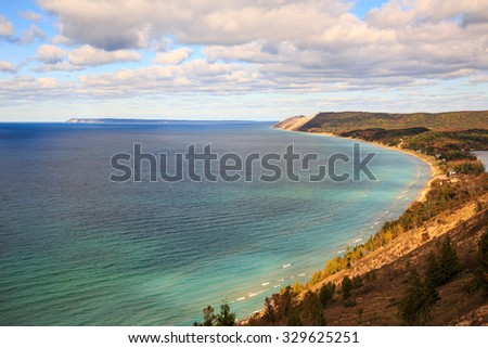 Sleeping Bear Dunes and South Manitou Island. Seen from Empire Bluff Trail in northern Michigan. Autumn colors dot the landscape and puffy clouds float in the blue sky. - stock photo