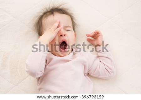 Sleeping beautiful and yawning baby toddler on the bed. Portrait - stock photo