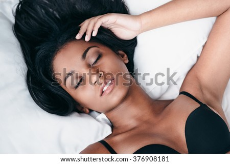 Sleeping beauty. Top view close-up of beautiful young African woman in black lingerie lying in bed and keeping eyes closed - stock photo