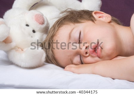 Sleeping boy and rabbit toy closeup