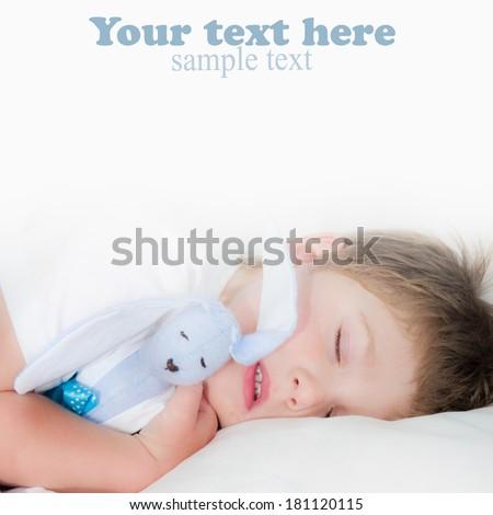 Sleeping boy and rabbit toy. Closeup portrait. - stock photo