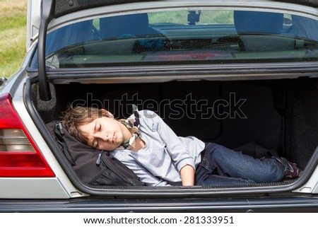Sleeping boy in the trunk of a car - stock photo