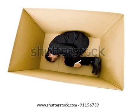 Sleeping Businessman inside a Cardboard Box - stock photo