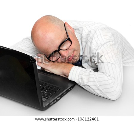 Sleeping businessman with laptop on a desk in the office. - stock photo