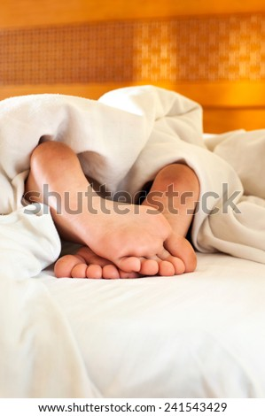 Sleeping child dirty feet on white bed linen from backside. Indoor.