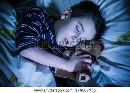 Sleeping child with his toy bear. - stock photo