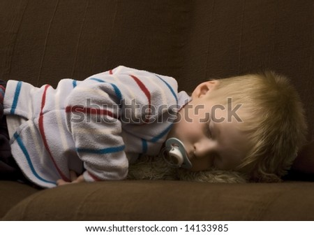 sleeping child with soother in his mouth.  (Desaturated for soft look) - stock photo