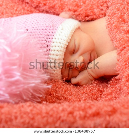 sleeping cute baby funny pink hat in soft fabric and smiling in sweet dreams, beautiful kid's face closeup