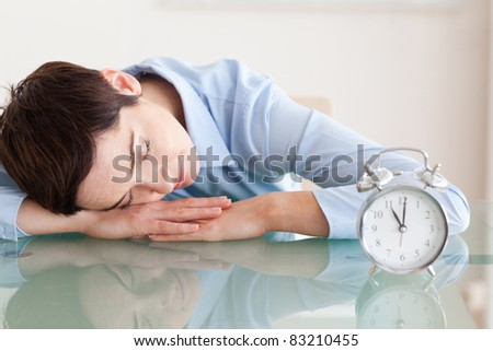 Sleeping cute brunette woman with her head on the desk next to an alarm clock in an office