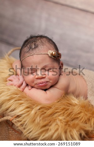 Sleeping eight day old newborn baby girl with puckered lips. She is sleeping on gold faux fur and wearing a pearl and feather headband. - stock photo