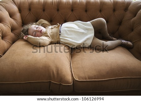 sleeping girl lying on a couch with arms up