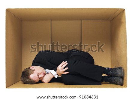 Sleeping in a cardboard box isolated on white background - stock photo