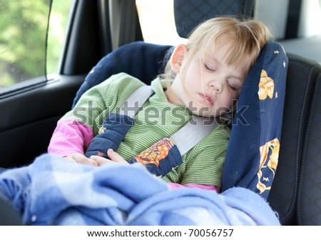sleeping little, blond hair girl in car seat - stock photo