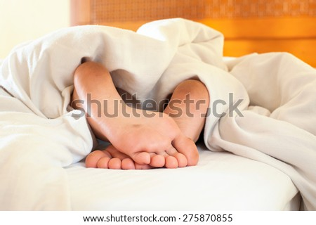 Sleeping little child funny dirty feet on white bed linen. Indoors closeup. - stock photo