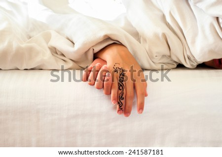 Sleeping little child hands on white bed linen. Indoors closeup. - stock photo