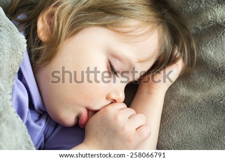 Sleeping little cute baby sucking thumb - stock photo