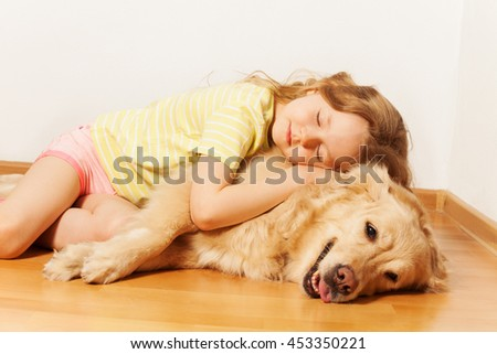 Sleeping little girl lying on her Golden Retriever