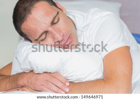 Sleeping man hugging his pillow at home in the bedroom - stock photo