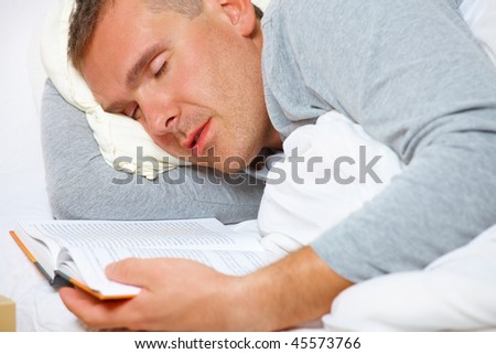 Sleeping man with open book on the bed