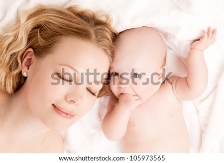 sleeping mother and her four months old daughter in bed at home, top view - stock photo