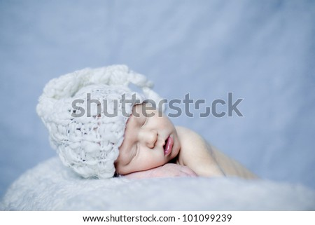 Sleeping newborn baby boy in a white hat on a blue background - stock photo