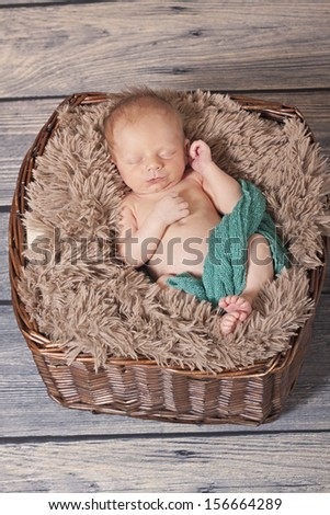 Sleeping newborn baby boy in a wicker basket with a soft fur blanket.