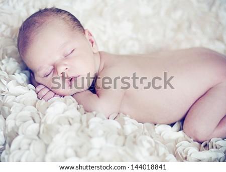 Sleeping newborn baby boy on tummy - stock photo