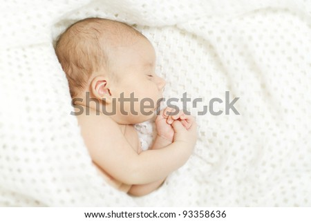 Sleeping newborn baby covered with white woolen blanket. - stock photo