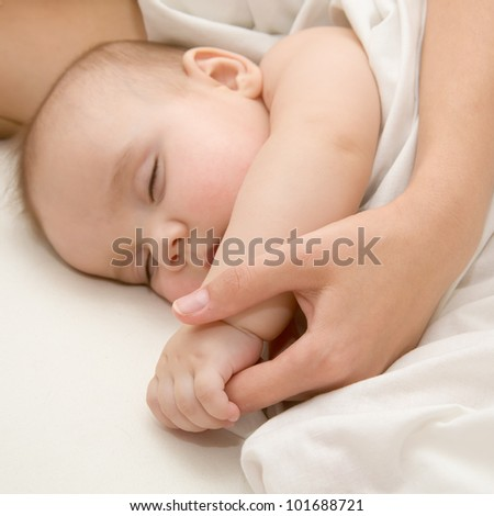 Sleeping newborn baby covered with white woolen blanket in bed. - stock photo