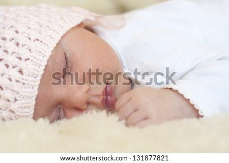 Sleeping newborn baby girl in pink hat  on fur. - stock photo