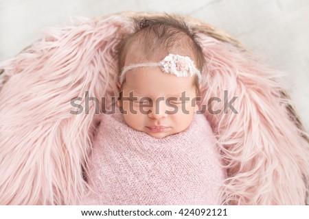 sleeping newborn baby in a basket - stock photo