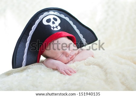 sleeping newborn baby in a pirate hat - stock photo