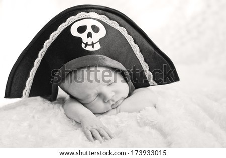 sleeping newborn baby in a pirate hat (soft focus, black and white ) - stock photo