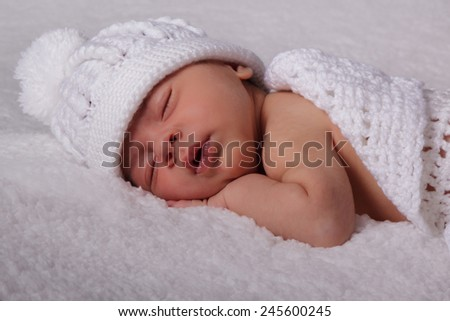 Sleeping newborn baby in a white hat on a white rug. Tenderness, peace - stock photo
