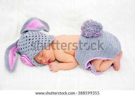Sleeping newborn baby in Easter rabbit costume on a knitted blanket